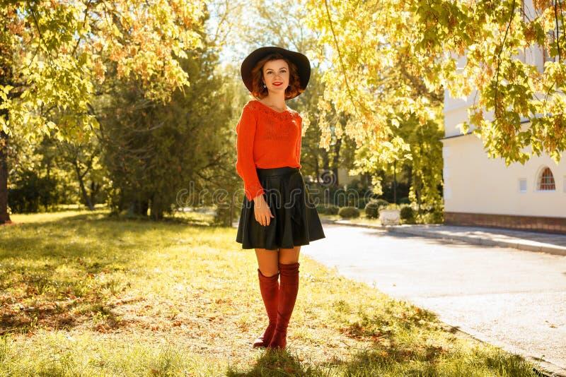 Mooie jonge vrouw in de herfstpark in zwarte hoed stock fotografie