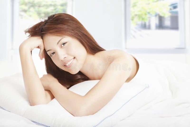 Mooie jonge vrouw in de slaapkamer stock foto