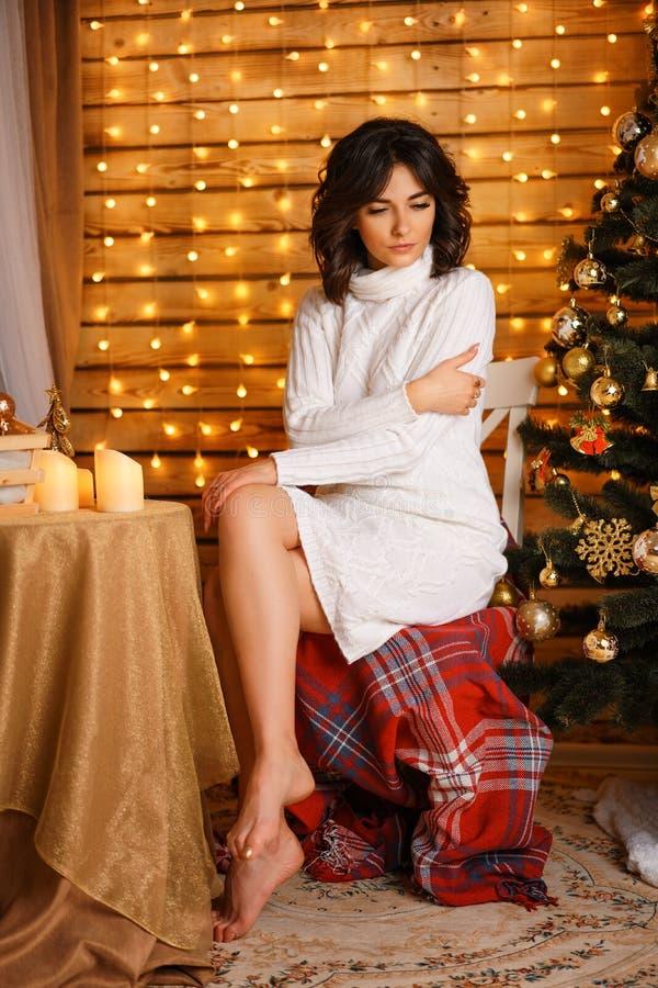 Mooie jonge vrouw dichtbij de Kerstboom in een witte sweater, comfortabel wachten voor nieuw jaar en Kerstmisvakantie stock foto's