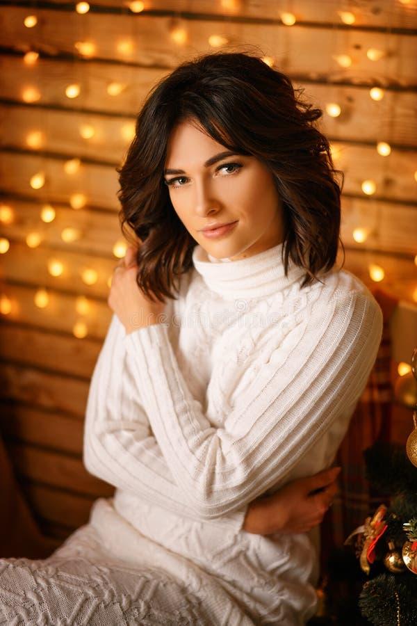 Mooie jonge vrouw dichtbij de Kerstboom in een witte sweater, comfortabel wachten voor nieuw jaar en Kerstmisvakantie royalty-vrije stock afbeelding