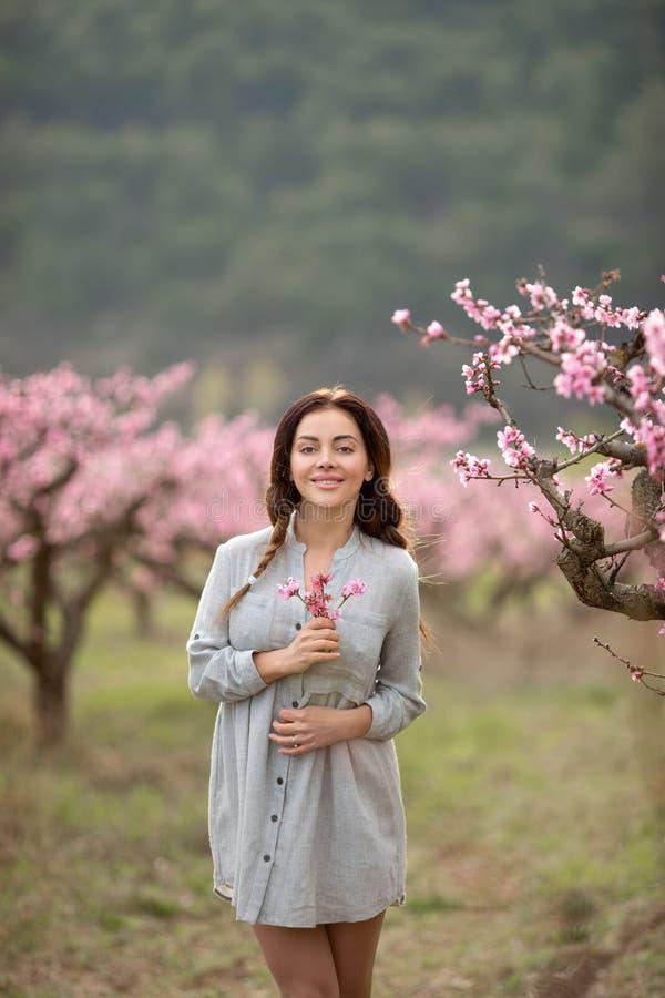 Mooie jonge vrouw dichtbij de tot bloei komende de lenteboom stock afbeelding