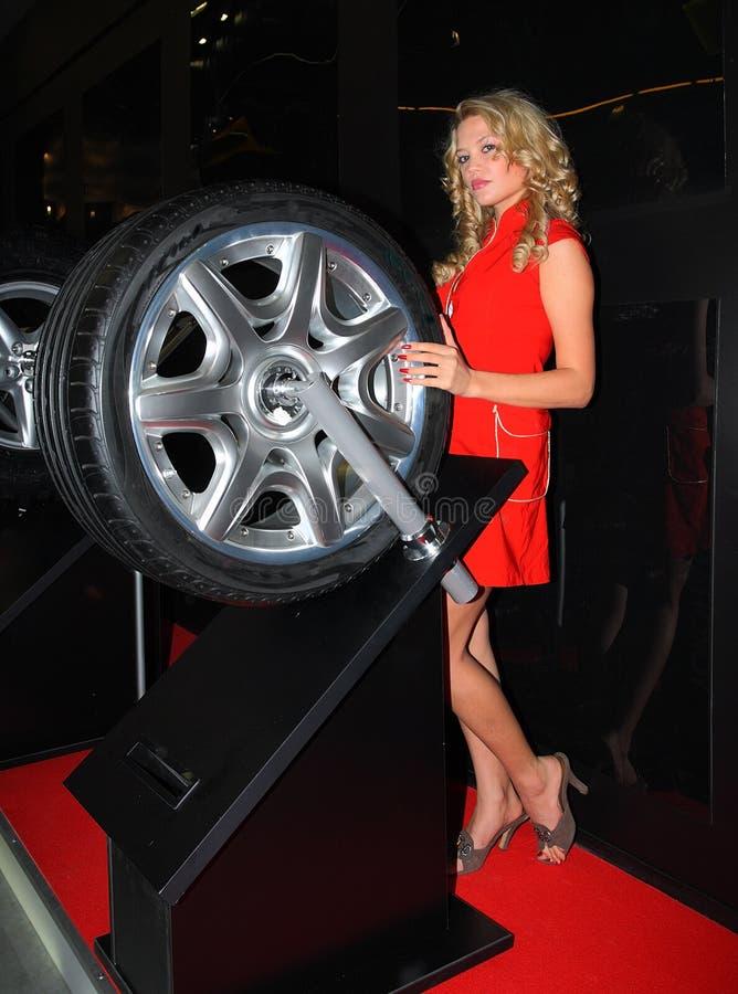 Mooie jonge vrouw dichtbij een autowiel. stock foto