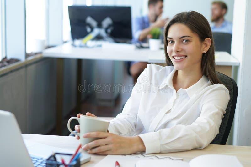Mooie jonge vrouw die aan haar laptop in haar bureau werken stock foto's