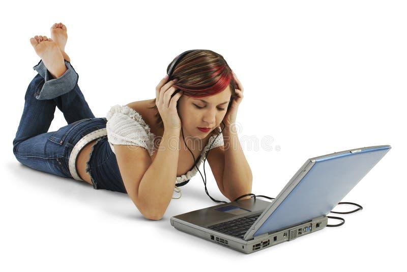 Mooie Jonge Vrouw die aan Hoofdtelefoons luistert stock fotografie