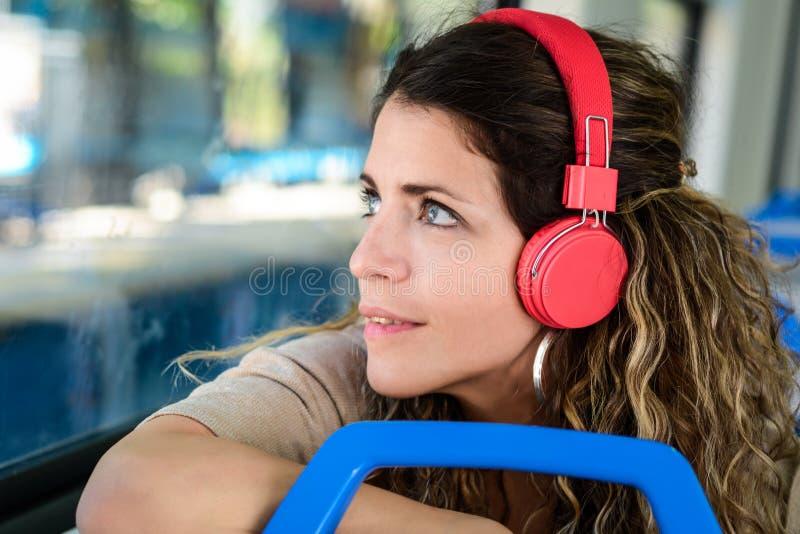 Mooie jonge vrouw die aan muziek in een trein luisteren stock afbeeldingen
