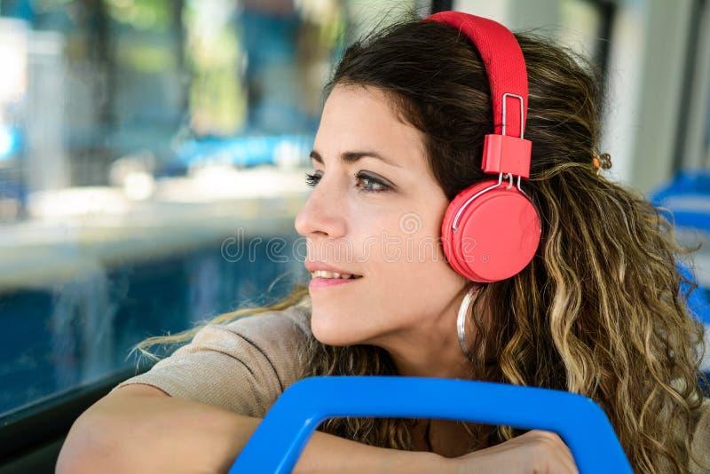 Mooie jonge vrouw die aan muziek in een trein luisteren stock foto