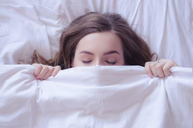Mooie jonge vrouw die in bed en het slapen liggen royalty-vrije stock fotografie