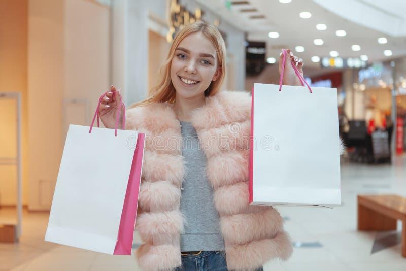 Mooie jonge vrouw die bij de lokale wandelgalerij winkelen stock fotografie