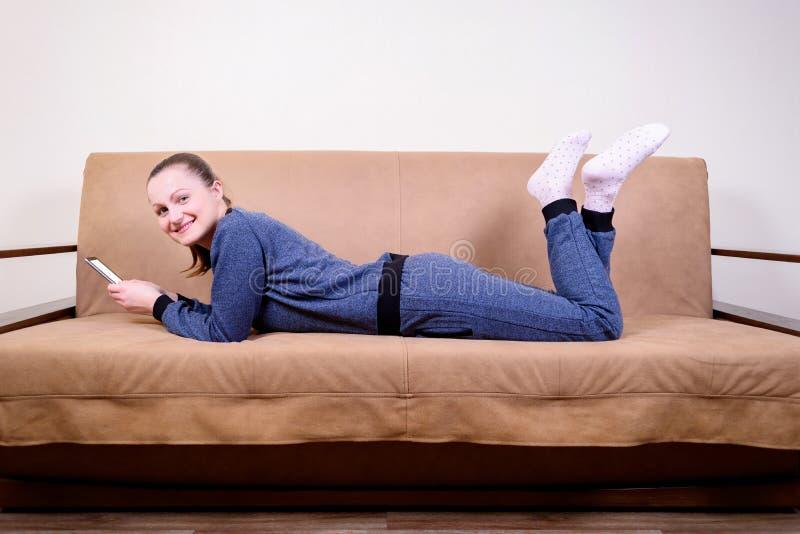 Mooie jonge vrouw die bij een bank, het gebruiken van een smartphone en het texting liggen royalty-vrije stock foto