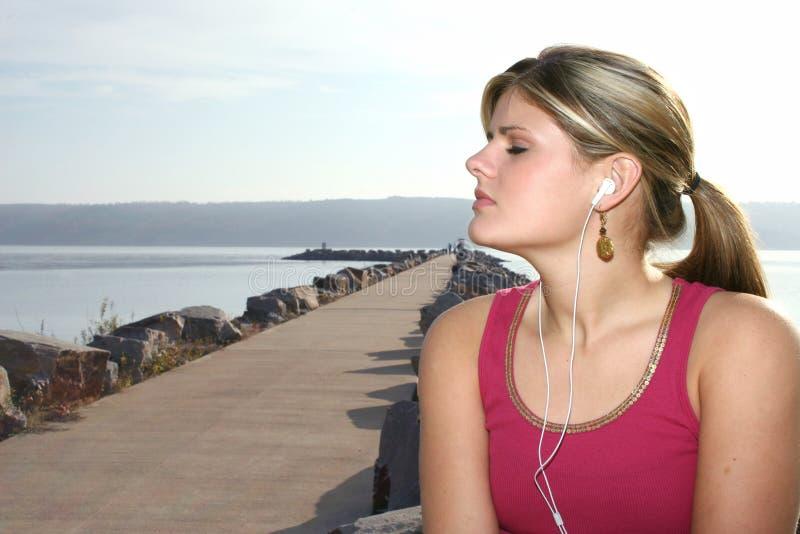 Mooie Jonge Vrouw die bij Park aan Muziek luistert stock fotografie