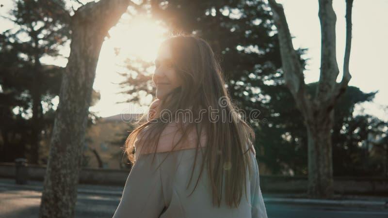 Mooie jonge vrouw die bij park in heldere de herfstdag lopen De vrouwelijke draaien en de glimlach bij camera aan somebody, genie royalty-vrije stock foto's