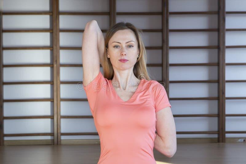 Mooie jonge vrouw die in binnenlandse zolder uitwerken, doend yogaoefening op blauwe mat, de oefening van het wapensaldo met gekr royalty-vrije stock foto's