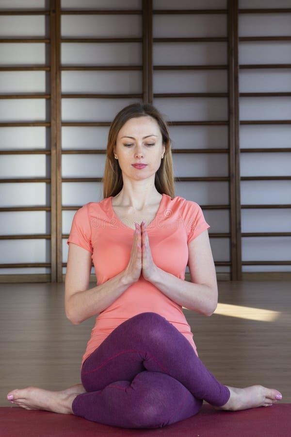 Mooie jonge vrouw die in binnenlandse zolder uitwerken, doend yogaoefening op blauwe mat, de oefening van het wapensaldo met gekr stock foto's