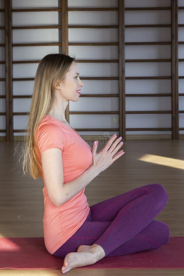 Mooie jonge vrouw die in binnenlandse zolder uitwerken, doend yogaoefening op blauwe mat, de oefening van het wapensaldo met gekr royalty-vrije stock afbeelding