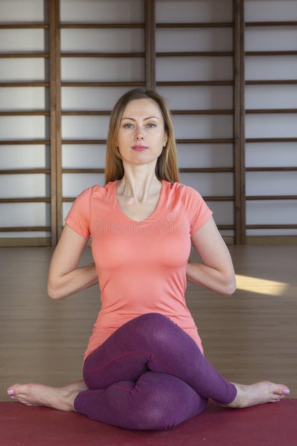 Mooie jonge vrouw die in binnenlandse zolder uitwerken, doend yogaoefening op blauwe mat, de oefening van het wapensaldo met gekr royalty-vrije stock fotografie