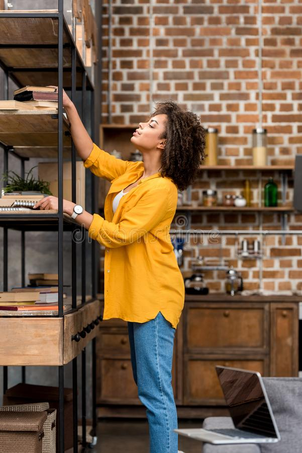 mooie jonge vrouw die boek van plank nemen royalty-vrije stock afbeelding