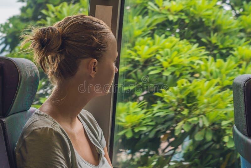 Mooie jonge vrouw die bus nemen aan het werk stock fotografie