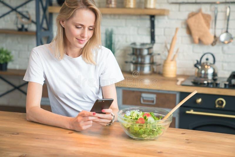 Mooie jonge vrouw die celtelefoon met behulp van terwijl het maken van salade in de keuken Gezond voedsel Plantaardige salade Die royalty-vrije stock afbeeldingen