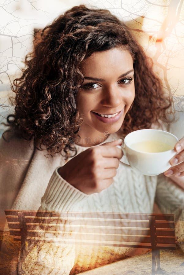 Mooie jonge vrouw die cheerfully terwijl het drinken van haar thee glimlachen royalty-vrije stock afbeeldingen