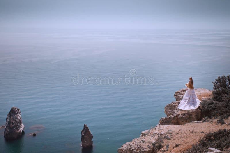 Mooie jonge vrouw die de kust bekijken Het is een zonsondergang en zij draagt een witte kleding royalty-vrije stock foto's