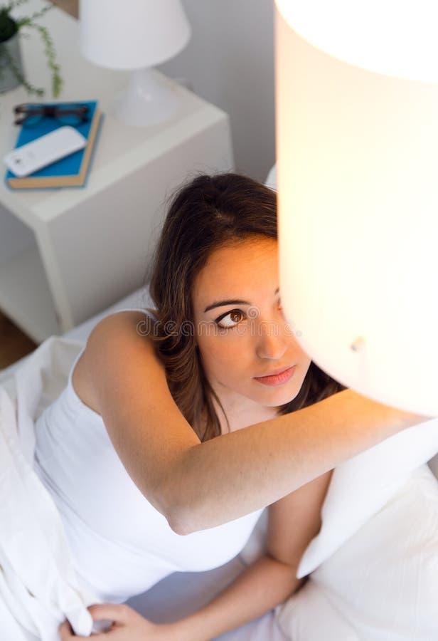 Mooie jonge vrouw die de lamp uitzetten royalty-vrije stock afbeeldingen