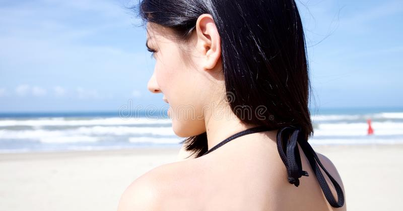Mooie jonge vrouw die de oceaan bekijken royalty-vrije stock afbeelding