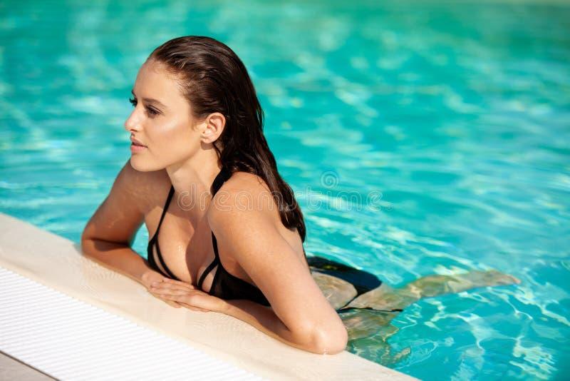 Mooie jonge vrouw die in de pool op een hete de zomerdag zwemmen royalty-vrije stock afbeelding