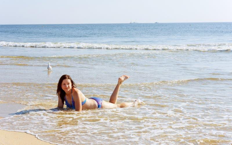 Mooie jonge vrouw die de woordliefde op het zand schrijven royalty-vrije stock afbeeldingen