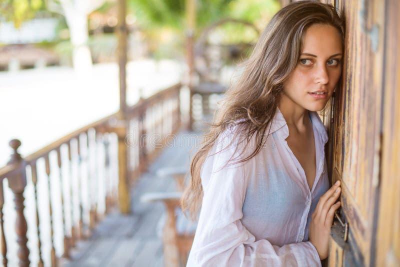 Mooie jonge vrouw die dichtbij de deur luisteren royalty-vrije stock foto's