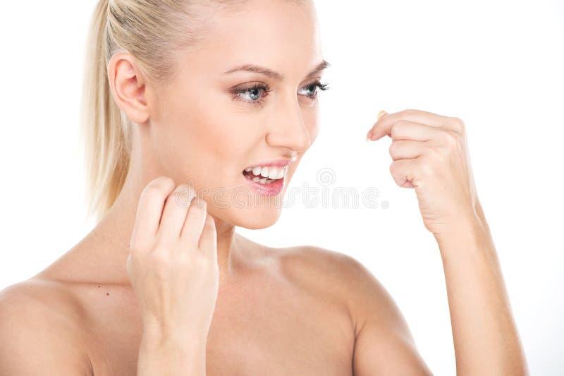 Mooie jonge vrouw die die tandzijde gebruiken, op wit wordt geïsoleerd stock afbeeldingen