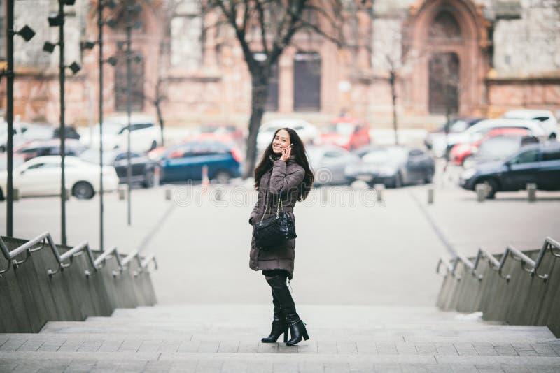 Mooie jonge vrouw die door mobiele telefoon op treden in openlucht in stad spreken stock afbeelding
