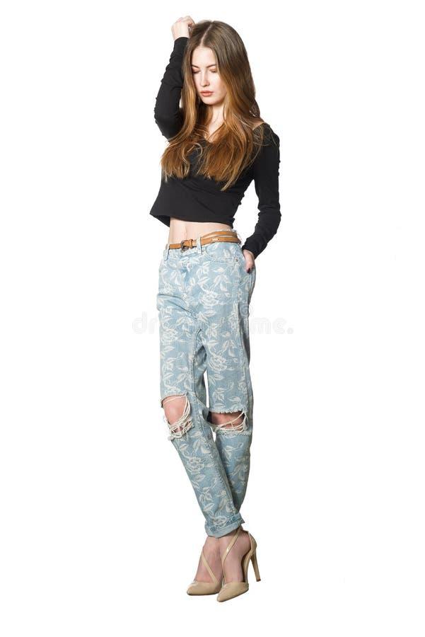 Mooie jonge vrouw die dragend zwarte t-shirt en jeans stellen stock afbeeldingen