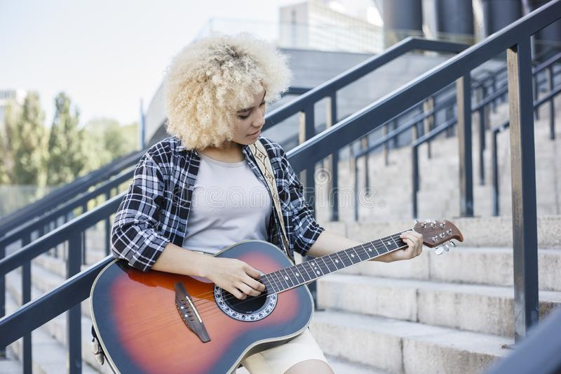 Mooie jonge vrouw die een akoestische gitaar spelen de straat stock fotografie