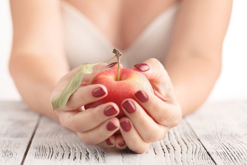 Mooie jonge vrouw die een appel houden stock afbeeldingen