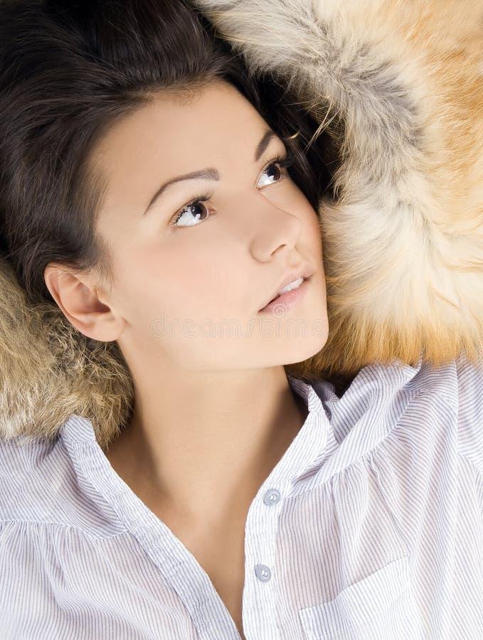 Mooie jonge vrouw die in een bont ligt royalty-vrije stock foto's