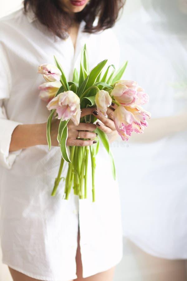 Mooie jonge vrouw die een bos van de gevoelige lente roze Turkije houden royalty-vrije stock foto