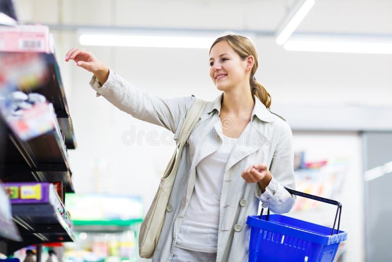 Mooie jonge vrouw die in een een kruidenierswinkelopslag/supermarkt winkelen royalty-vrije stock afbeeldingen