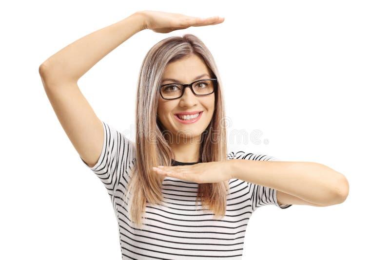 Mooie jonge vrouw die een kader met handen boven en onder haar hoofd gesturing stock afbeelding