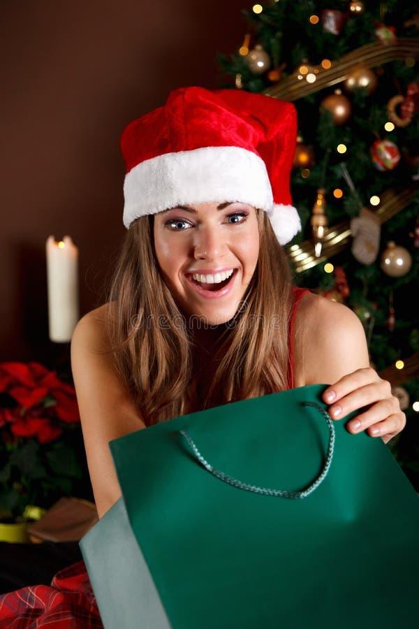 Mooie jonge vrouw die een Kerstmisgift opent royalty-vrije stock foto's