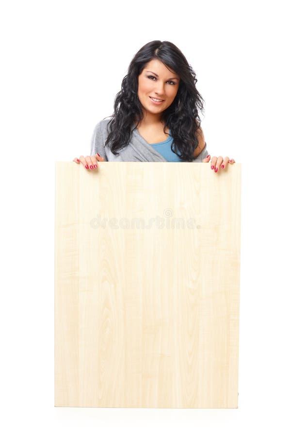 Mooie jonge vrouw die een lege houten raad houdt royalty-vrije stock fotografie
