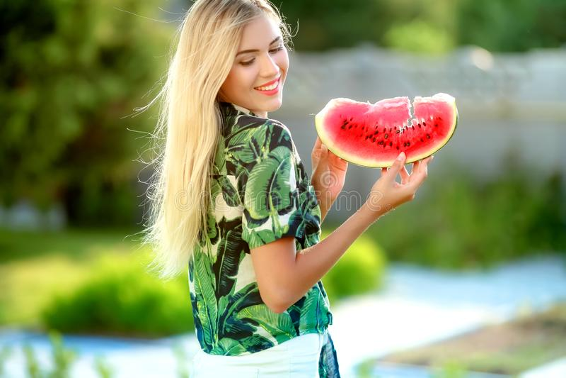 Mooie jonge vrouw die een plak van watermeloen tonen Zij is Kaukasisch De zomer en levensstijlconcepten royalty-vrije stock afbeelding