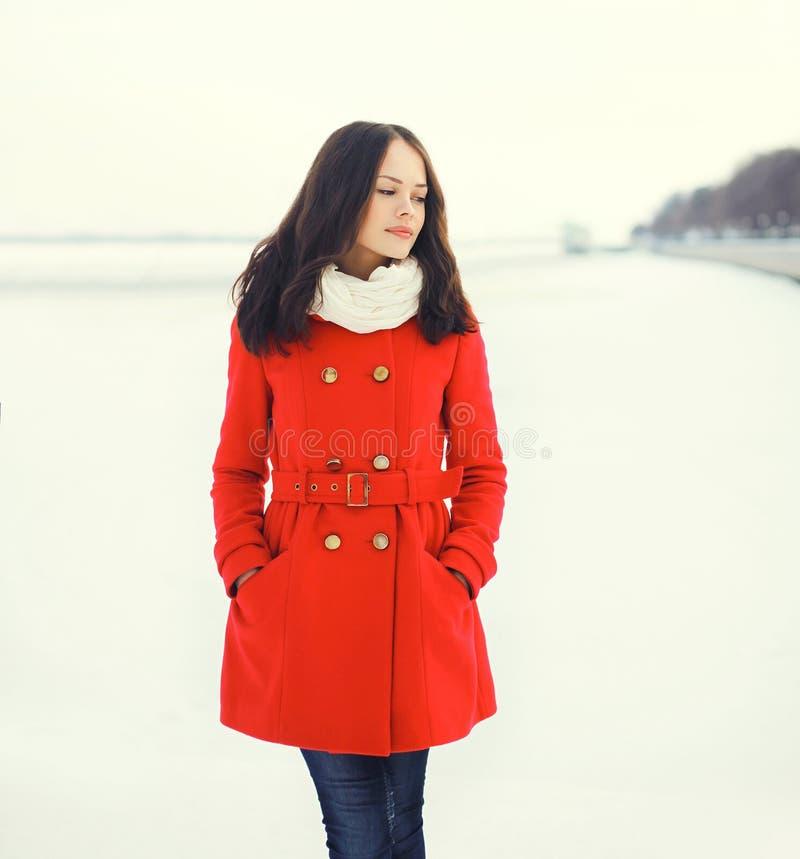 mooie jonge vrouw die een rode laag en een sjaal over sneeuw in de winter dragen royalty-vrije stock afbeeldingen