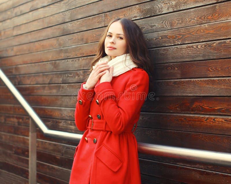 Mooie jonge vrouw die een rode laag in stad dragen royalty-vrije stock afbeelding