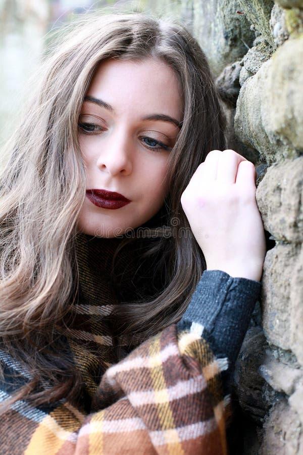 Mooie jonge vrouw die een sjaal dragen die tegen een steen leunen wa stock fotografie