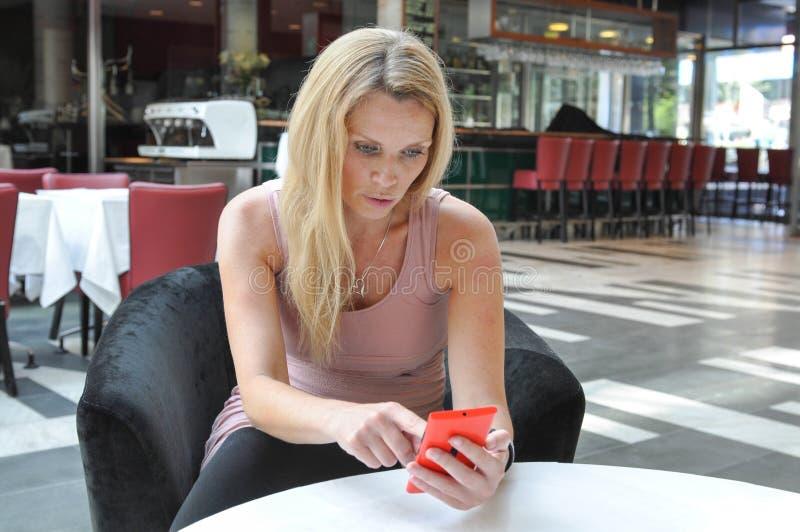 Mooie jonge vrouw die een slimme telefoon met behulp van