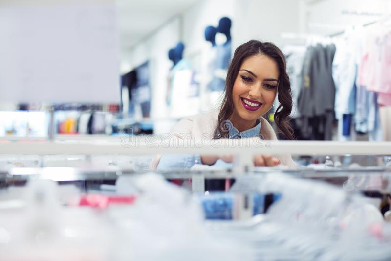 Mooie jonge vrouw die in een warenhuis winkelen stock afbeelding