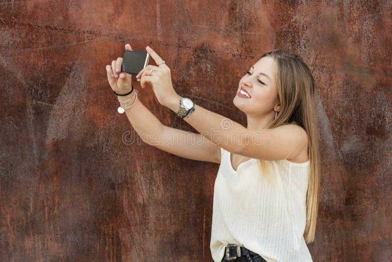 Mooie jonge vrouw die een zelfportret nemen stock foto's