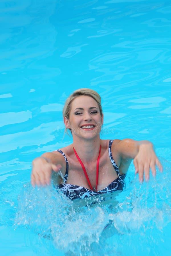 Mooie jonge vrouw die in een zwembad glimlachen, stock foto's