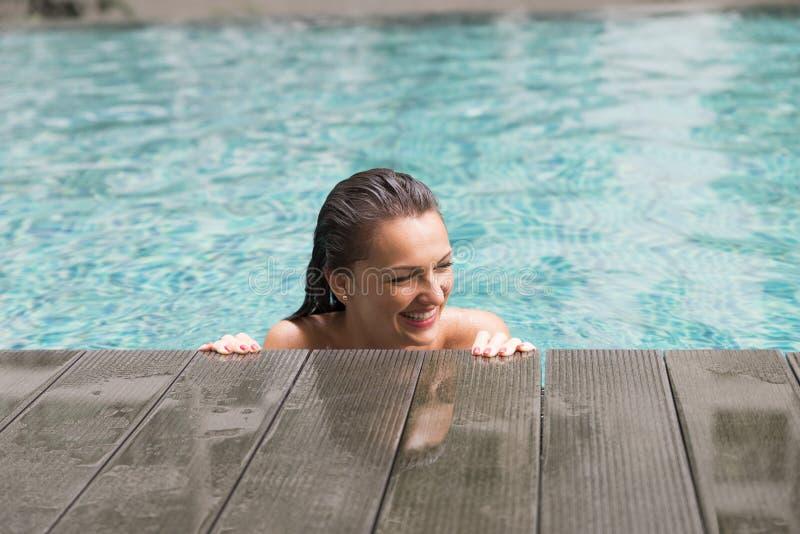 Mooie jonge vrouw die in een zwembad glimlachen stock foto
