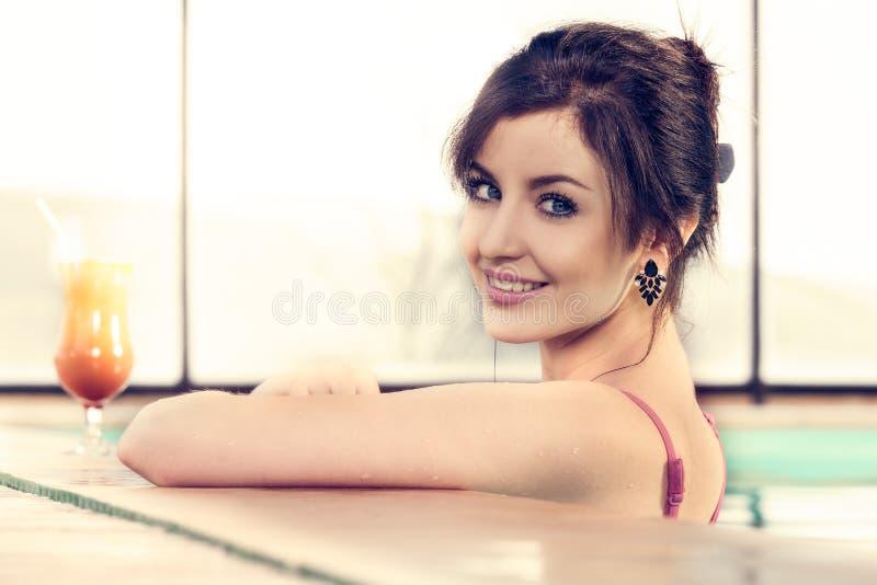 Mooie jonge vrouw die in een zwembad glimlachen stock foto's
